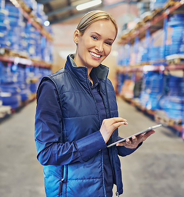 Portrait of a woman using a digital tablet in a large warehouse